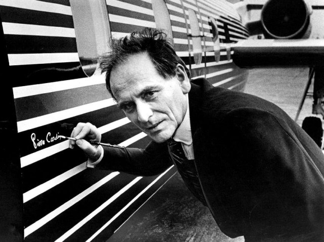 Pierre Cardin puts his signature to the side of a plane circa the late 1970s